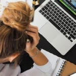 Stressed woman holding her head, staring down at her desk